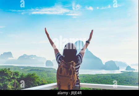 Happy young traveler woman backpacker raised arm up to sky enjoying a beautiful of nature at top of mountain view - Stock Photo