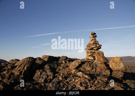 Inukshuk or Inuksuk at the top of the mountain along a hiking trail near the community of Qikiqtarjuaq, Broughton - Stock Photo