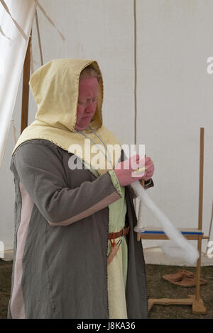 Woman dressed in traditional costume spinning wool in tent at replica of Viking settlement - Stock Photo