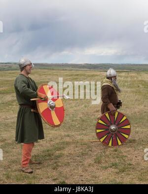 Men wearing traditional Viking warrior costumes during battle reenactment - Stock Photo