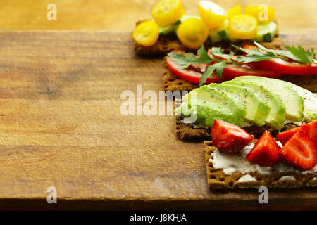 Sandwiches rye crisp with avocado, tomato and strawberry - Stock Photo