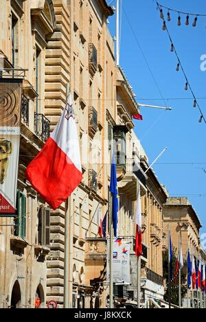 EU and Maltese flags and buildings along Republic Street aka Triq Ir Repubblika, Valletta, Malta, Europe. - Stock Photo