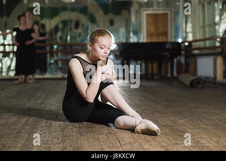 Young ballet dancer practicing in class. Ballerina doing exercises. Girl stretches herself in the dancing hall. - Stock Photo