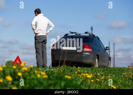 Man near car on road - Stock Photo