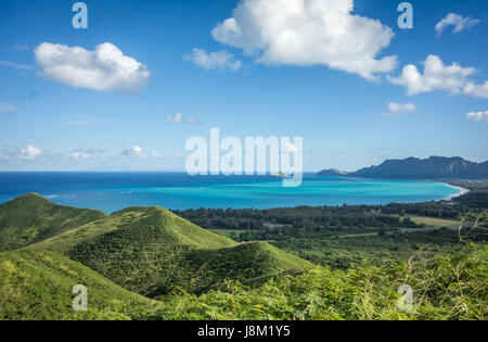 The lush green mountains and beautiful turquoise ocean water of Waimanalo Bay, Hawaii, as seen from the top of the - Stock Photo