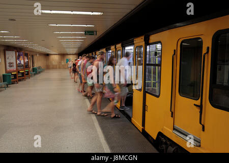 Passengers getting on to a yellow Metro Line 1 (Földalatti) train in Budapest, Hungary. - Stock Photo