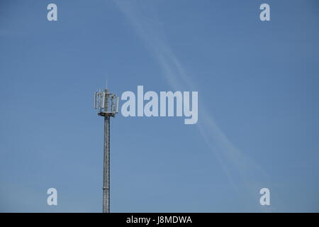 Telecommunications cell phone tower with antennas against a blue sky background - Stock Photo