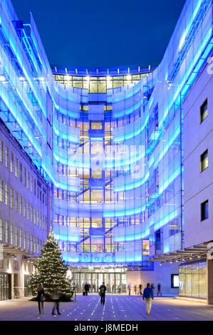 New BBC eastern extension building beside original Broadcasting House lit with blue lighting with Christmas tree - Stock Photo