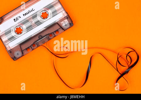Retro cassette tape which has the wording 80's music wrote on it and part of the tape reel unfurled out of the cassette - Stock Photo