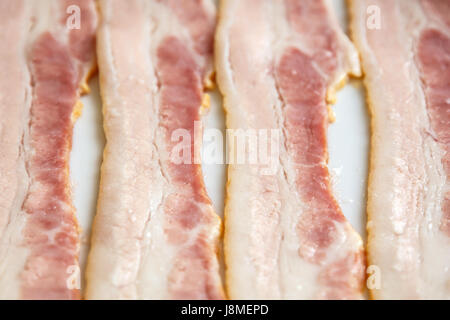 strip of fresh raw bacon close up, selective focus - Stock Photo