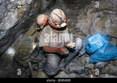 Potosi, Bolivia - November 29, 2013: Two miners looking for silver in the silver mine of the Cerro Rico in Potosi, - Stock Photo