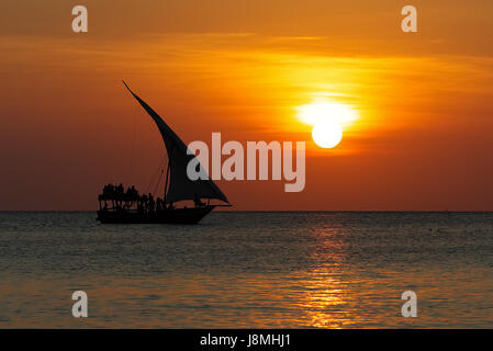 Stunning sunset captured north on Zanzibar, Tanzania, Africa. Sailboat passing by. - Stock Photo