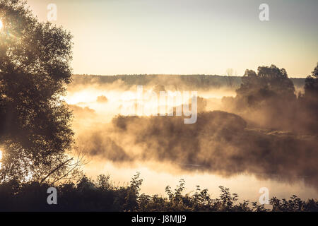 Misty rural landscape during golden hour at river bank in the early morning - Stock Photo