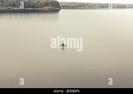 Exploring man in boat in the middle of vast expanses of tranquil lake. Symbolizing loneliness and searching - Stock Photo