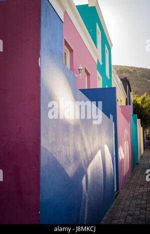 Sunshine reflecting of the colourful walls of the houses in the Bo-Kaap neighbourhood in Cape Town, South Africa - Stock Photo