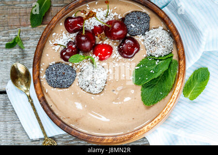 Chocolate smoothie bowl with cherry, mint and energy balls. Love for a healthy vegan food concept - Stock Photo