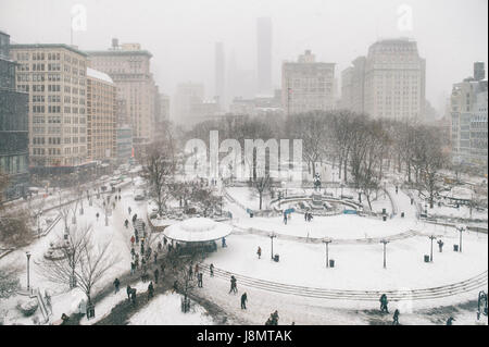 Snowy winter scene with trails left by pedestrians in the snow in Union Square as a blizzard overtakes New York - Stock Photo