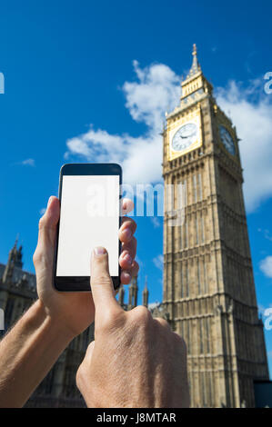 Hand touching screen of blank mobile phone in front of Big Ben and Westminster Palace in London under bright blue - Stock Photo