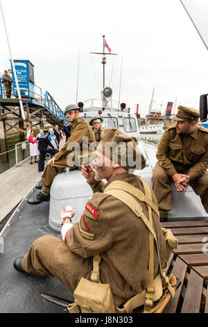 Dunkirk evacuation re-enactment at Ramsgate, England. Wounded and evacuated British soldiers  sitting on boat small - Stock Photo
