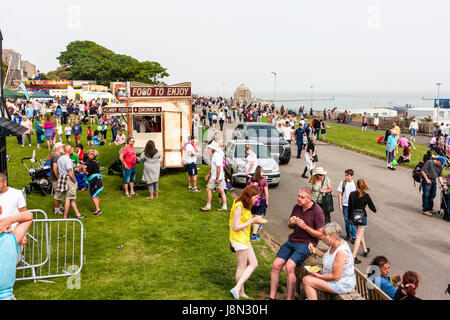 England, Ramsgate. Crowds on the sea front on the grass enjoying the hot weather and food stalls set up for an event. - Stock Photo