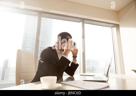 Man looking at laptop screen through VR headset