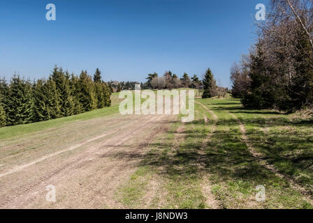 spring mountain meadow with dirty roads, trees around and clear sky near Vrchrieka hill in Javorniky mountains in - Stock Photo