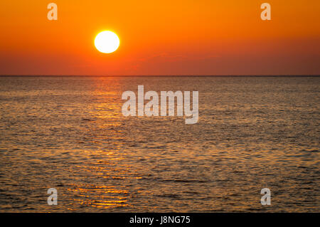 Golden sun reflects on calm seas in a classic Caribbean sunset from the Malecon in Havana, Cuba - Stock Photo
