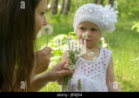 Happy mother and little daughter in the park - Stock Photo