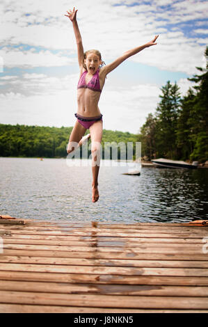 young teenage girl jumping off a dock at a lake in Ontario's cottage country - Stock Photo