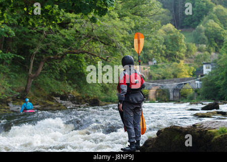 Female kayaker standing and watching the rapids on at the Serpents Tail near the Chain Bridge on the River Dee in - Stock Photo
