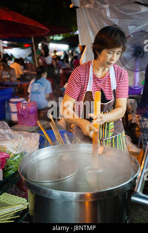 CHIANG MAI, THAILAND - AUGUST 27: Woman cooks at the Sunday Market (Walking Street) on August 27, 2016 in Chiang - Stock Photo