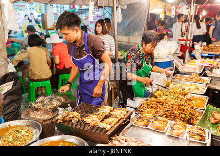 CHIANG MAI, THAILAND - AUGUST 27: Man cooks prawns on the grill at the Sunday Market (Walking Street) on August - Stock Photo