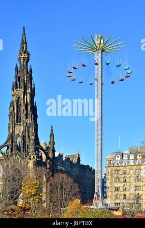 Edinburgh star flyer type fairground ride operating beside the Victorian Scott Monument at the annual European Christmas - Stock Photo