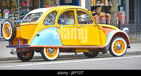 Citroen 2cv French car well maintained in unusual colours with rear mounted extended boot box & tow bar seen on - Stock Photo
