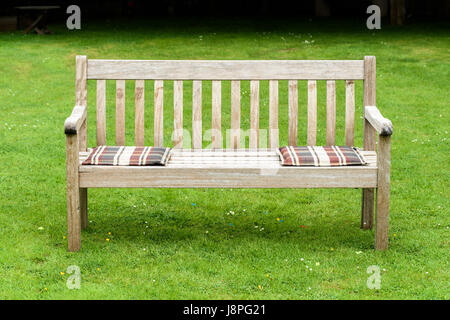 Wooden garden bench on lawn with large borders in country garden ...