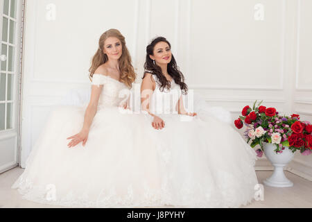 two brides in wedding dresses sit on a white couch - Stock Photo