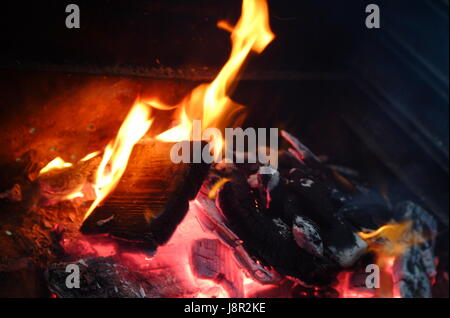 Burning wooden log flame on fire in fireplace - Stock Photo