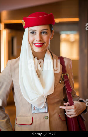 Young attractive Emirates cabin crew and flight attendant at London Heathrow Airport awaiting Emirates Airline A380 - Stock Photo