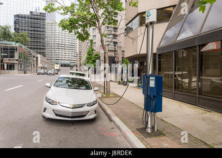 Montreal, CA - 27 May 2017: Chevrolet Volt electric car plugged into an EV charging station in Downtown Montreal - Stock Photo