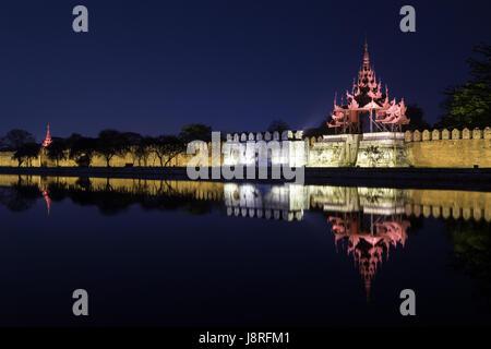 Lit citadel's wall, bastion and pyatthat (spire) and moat at the royal Mandalay Palace in Mandalay, Myanmar (Burma) - Stock Photo