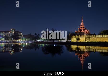 City and lit citadel's wall, bastion and pyatthat (spire) and moat at the royal Mandalay Palace in Mandalay, Myanmar - Stock Photo