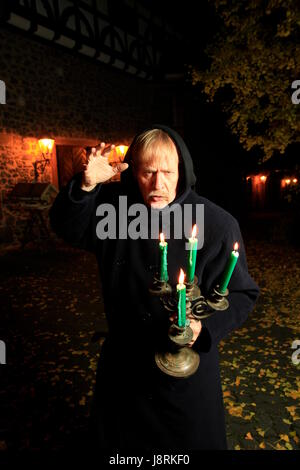 monk with candle holders - Stock Photo
