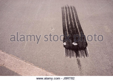 Black Tire Tracks On The Pavement - Stock Photo