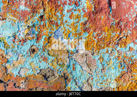 Close up of chipped peeling colorful paint on old wall - Stock Photo