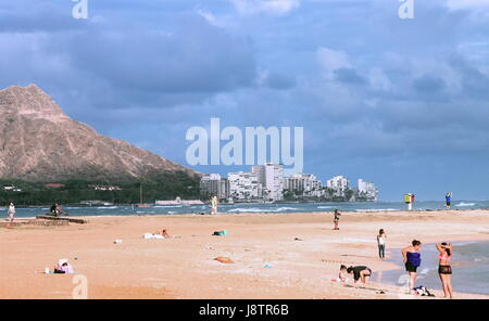People enjoying the beach at Ala Moana, Magic Island, with Waikiki and Diamond Head in the background. - Stock Photo