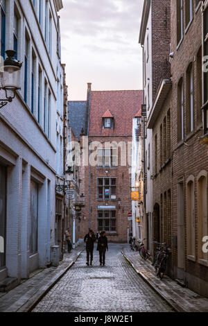 Two people walk down a charming side street in Bruges, Belgium on a cloudy day, with historic houses lining the - Stock Photo