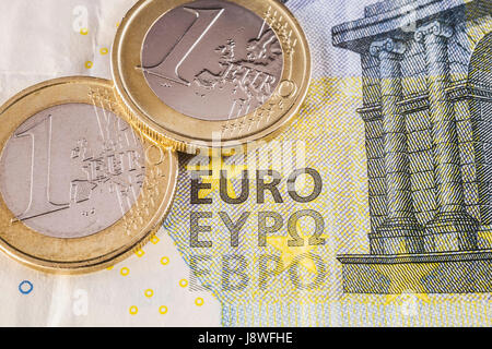 Two one Euro coins on top of five Euros paper currency bank note - Stock Photo