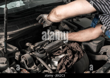 Spark plug replacement work. the mechanic in the garage. dirty real frame - Stock Photo
