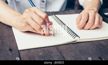 Woman hand writing note pad on wood table in coffee shop. - Stock Photo