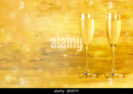 Two glasses of champagne on blurred golden background - Stock Photo